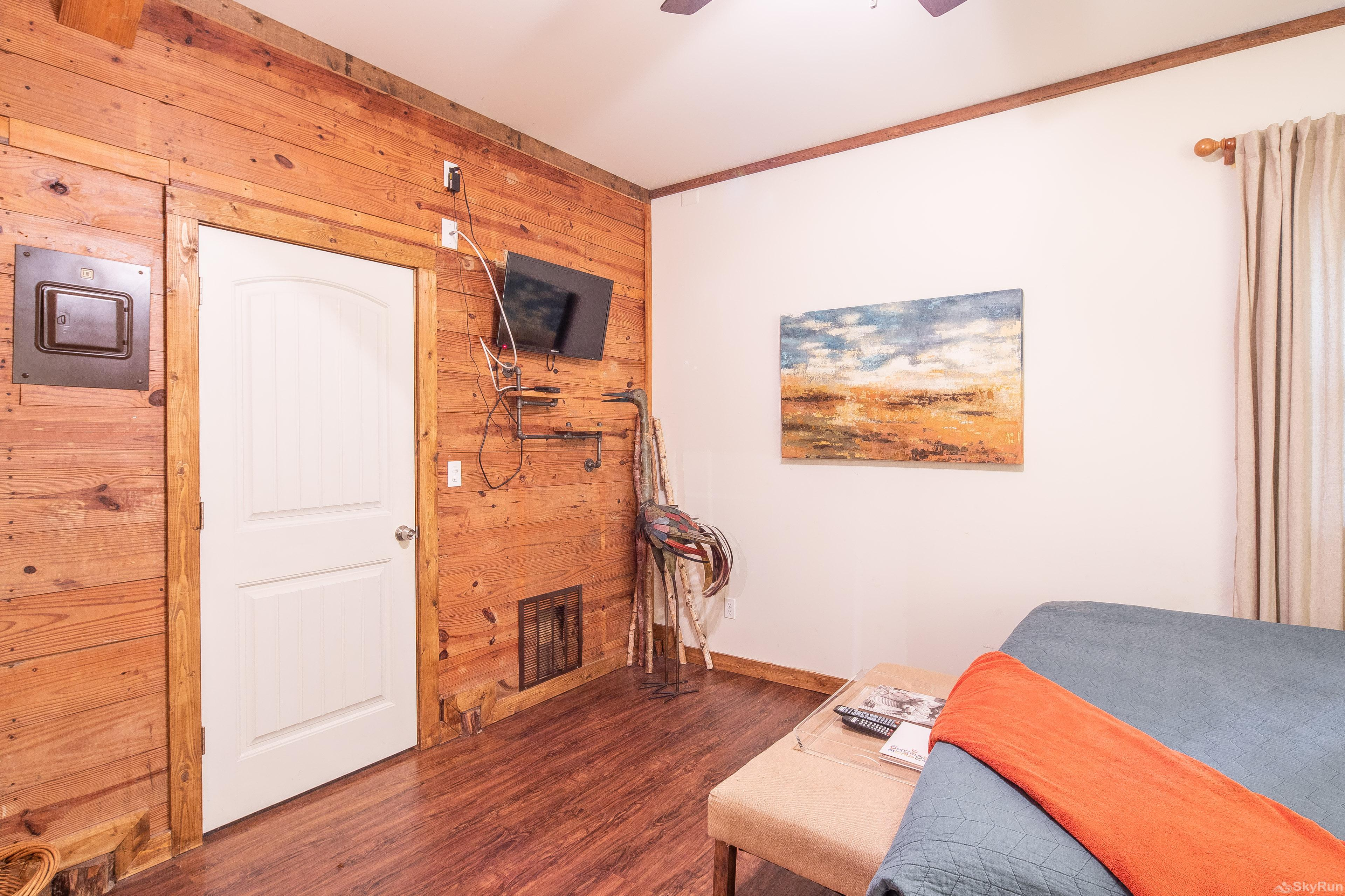 SUNSET RIVER HAUS Wall- mounted TV in first bedroom